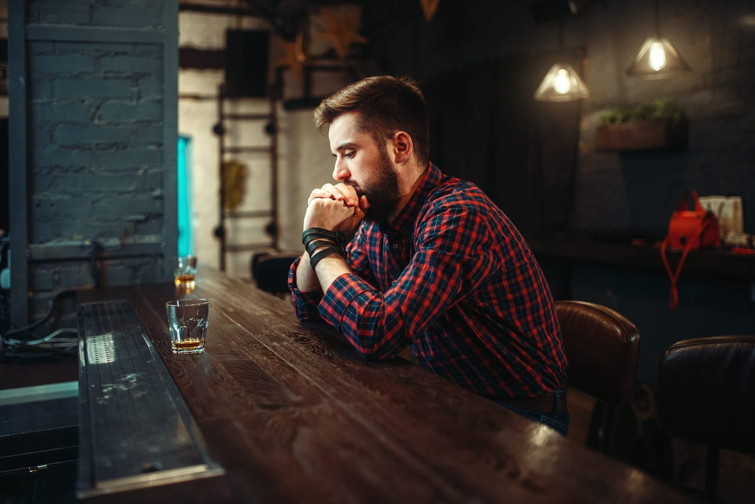 man in bar thinking about quitting alcohol