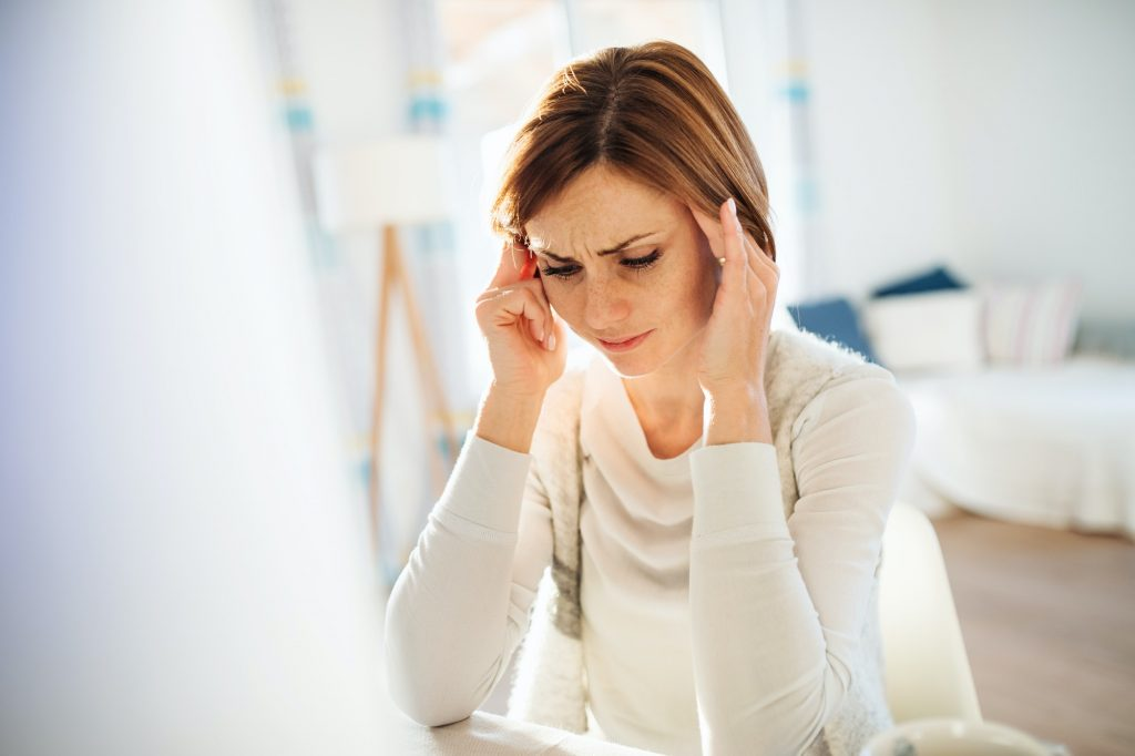 A young woman in pain sitting indoors, working in a home office.