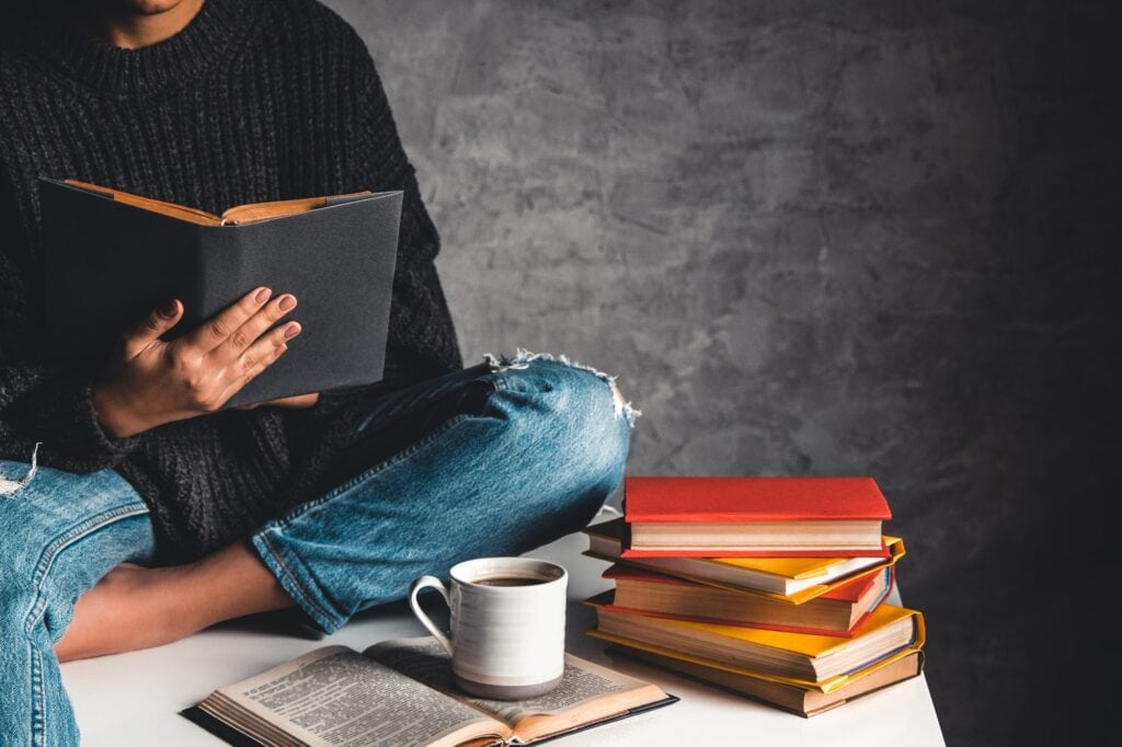 Girl reads books, study, develop with a cup of coffee on a white table and a gray background